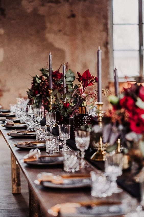 a chic Halloween wedding tablescape with a black runner, black plates and grey candles, burgundy blooms and greenery