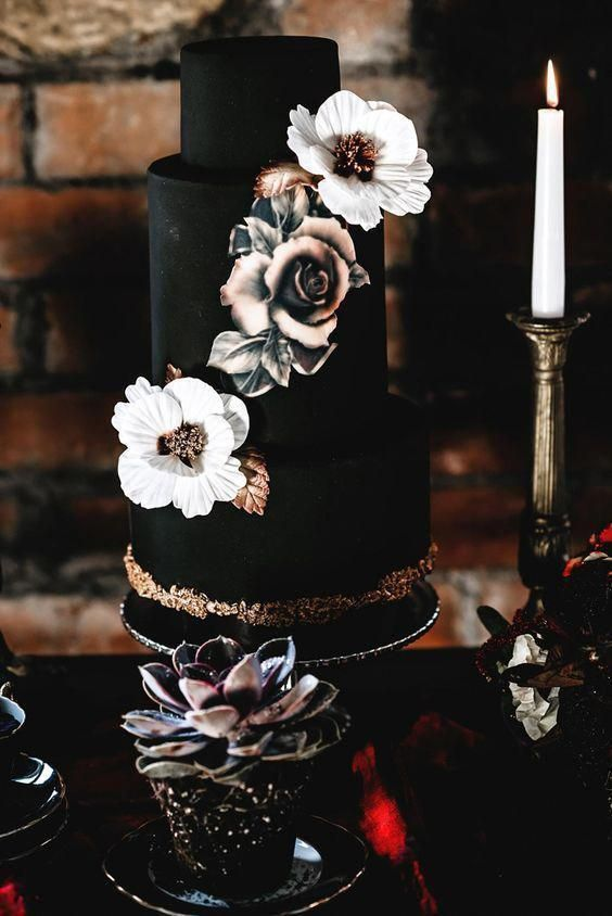a chic black wedding cake with white and tan sugar blooms and gold leaves plus gold glitter for Halloween