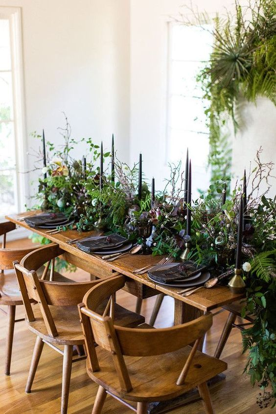 a chic moody wedding tablescape with a dimensional and textural greenery runner, black candles, napkins and plates