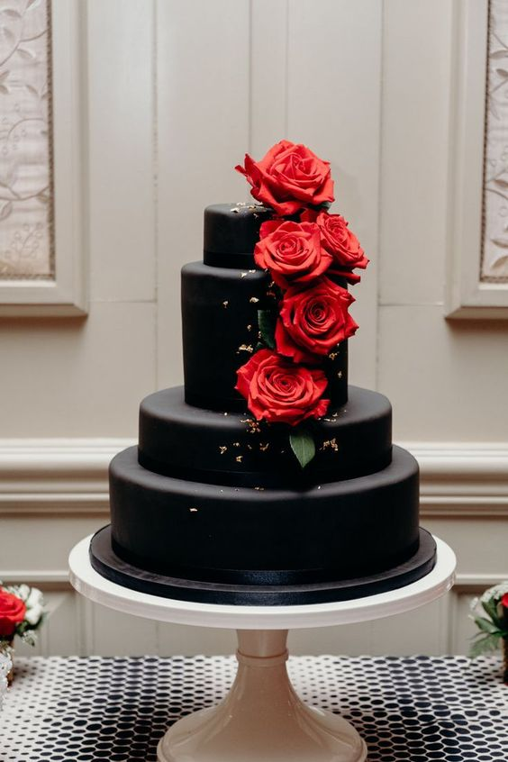 a classic dark chocolate wedding cake with gold leaf and red roses is ultimate romance and it never goes out of style