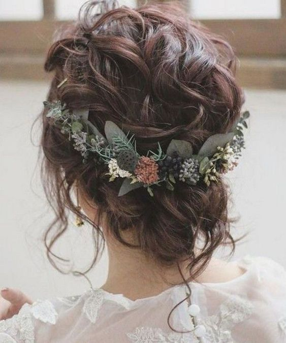 a cool and very messy and wavy wedding updo with some locks down and a greenery accent with neutral blooms is amazing for the fall