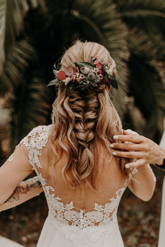 a cool wedding half updo with locks down and a large and thick braid, with neutral and red blooms for an accent