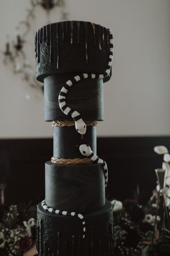 a creative All Hallows Eve black wedding cake with gold drip and black and white snakes is fabulous