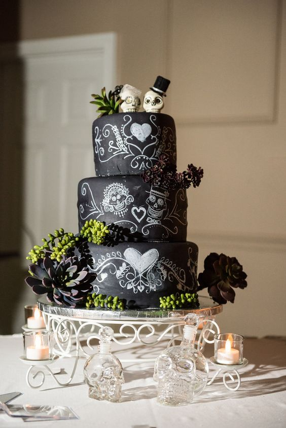 a creative chalkboard wedding cake with painted skulls, greenery, succulents and sugar skull toppers for a Halloween celebration