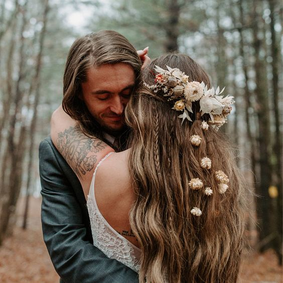 a creative fall boho wedding hairstyle with waves and braids, with dried flowers and leaves for an accent is amazing