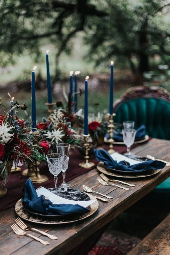 a dark romance Halloween wedding tablescape with teal napkins and candles, a burgundy runner and floral arrangements plus gold