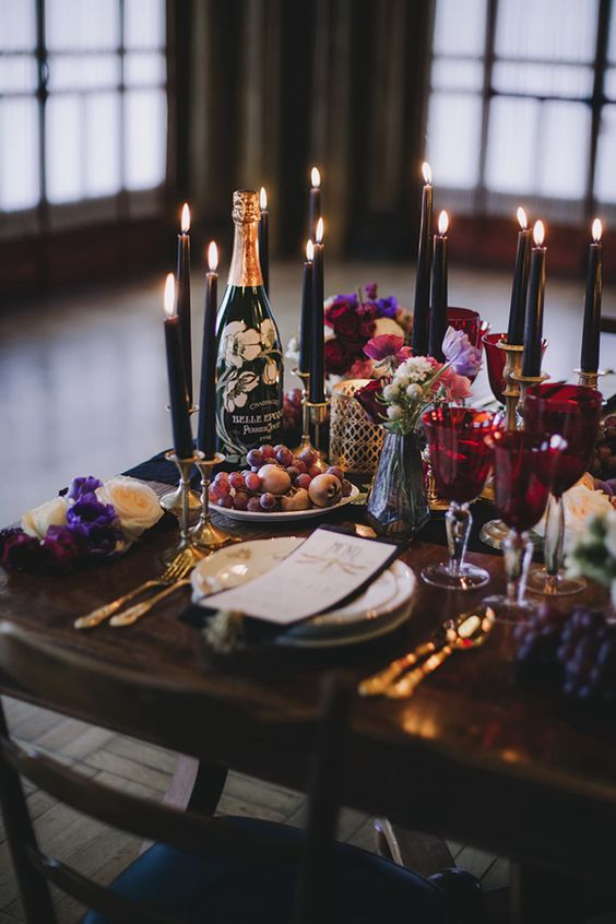a decadent Halloween wedding tablescape with black candles, gold cutlery, red goblets, bright blooms and fruits