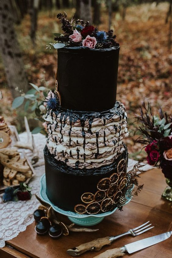 a gorgeous Halloween wedding cake with black tiers and a pavlova one, dried citrus, fresh blooms and greenery