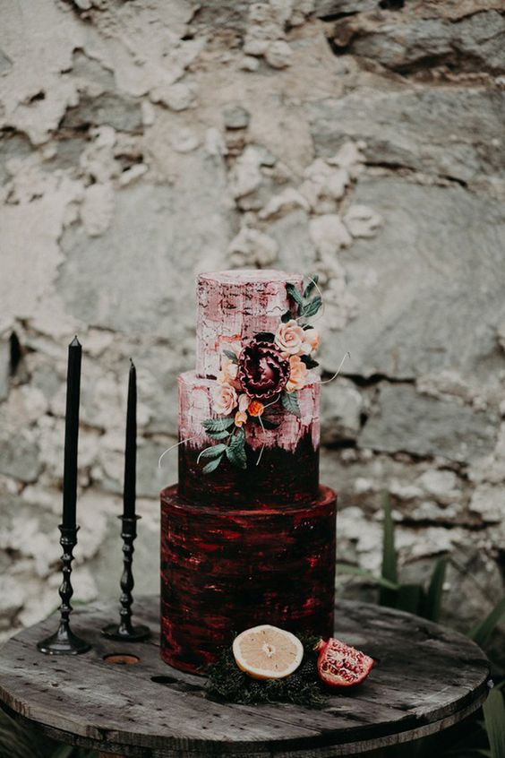 a gorgeous burgundy and pink wedding cake with patterns and sugar blooms and leaves for a Halloween wedding
