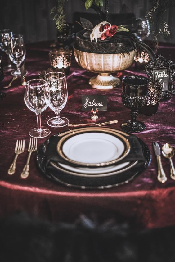 a gothic Halloween wedding tablescape with a purple tablecloth, gold touches, a bowl with a skull and blooms