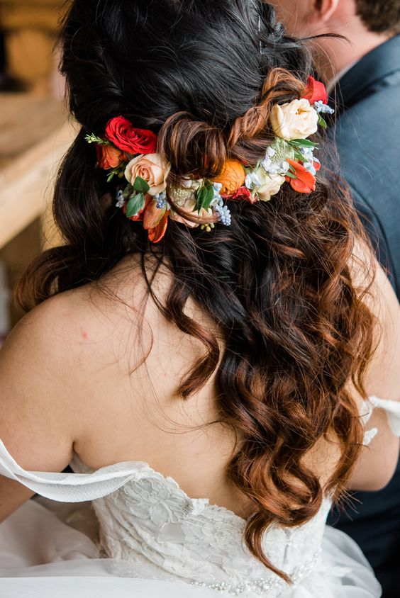a half updo on long hair, with braids and waves down, with super bright blooms and greenery for a bold fall wedding