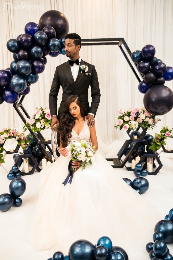 a hexagon wedding arch decorated with black, midnight blue and slate blue balloons and blooms