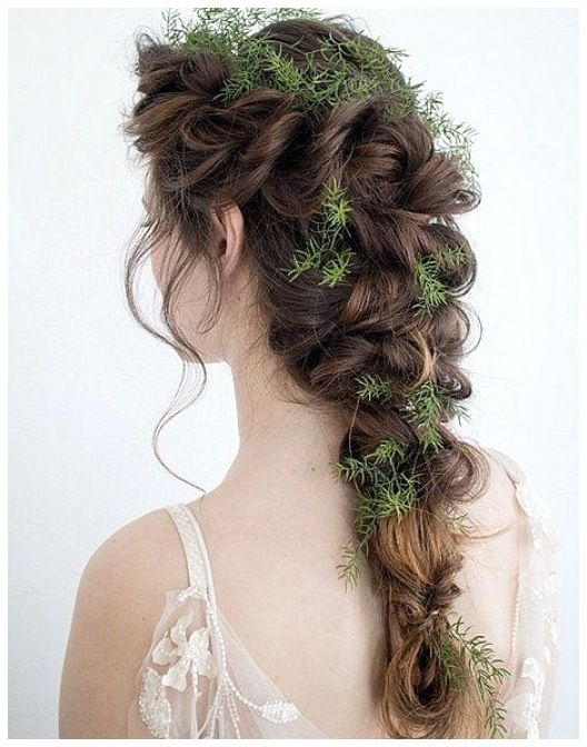 a loose messy twisted braid with greenery tucked in is a great solution for a fall woodland bride