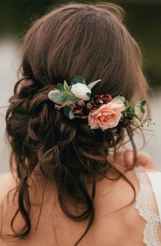 a low and messy updo with twists and braids, locks down and pink and burgundy blooms for an accent is amazing for the fall