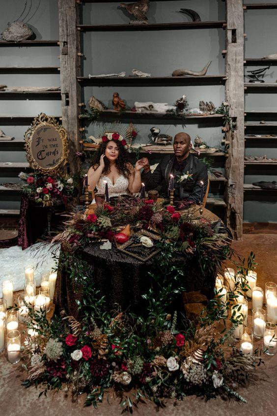 a lush decadent Halloween table with greenery and dark blooms, black candles and greenery and some fruits