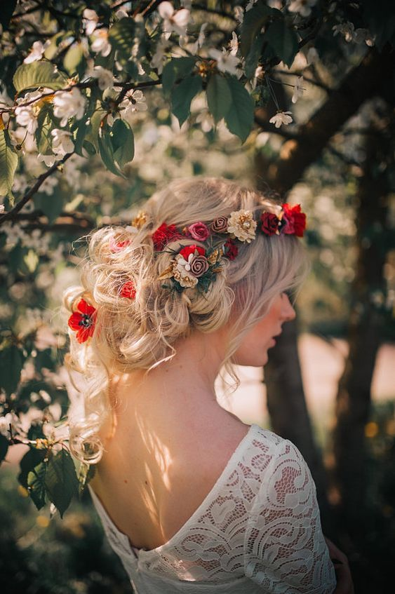 a messy and loose low updo with lots of waves and twists, bold red, pink and neutral blooms tucked in will work for both summer or fall wedding