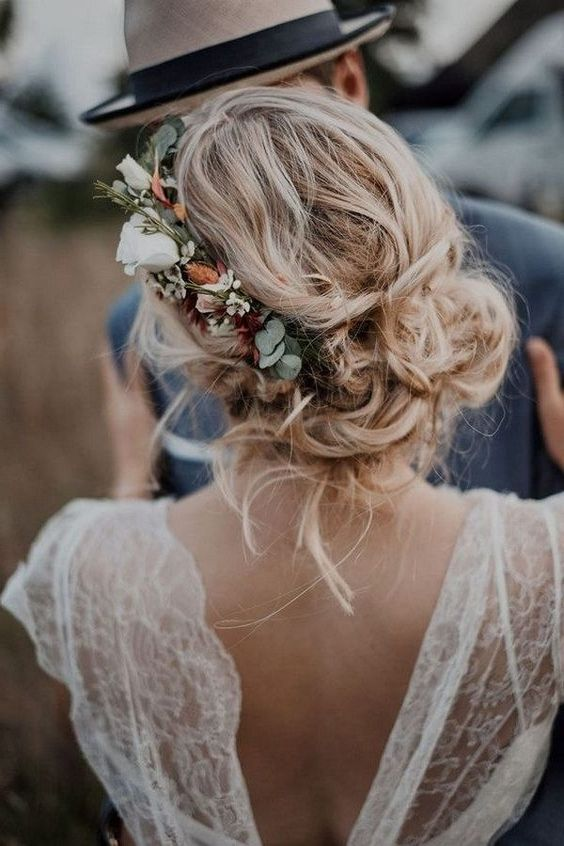 a messy and loose wedding low updo with waves and locks down and with a floral accent - neutral and blush blooms and greenery
