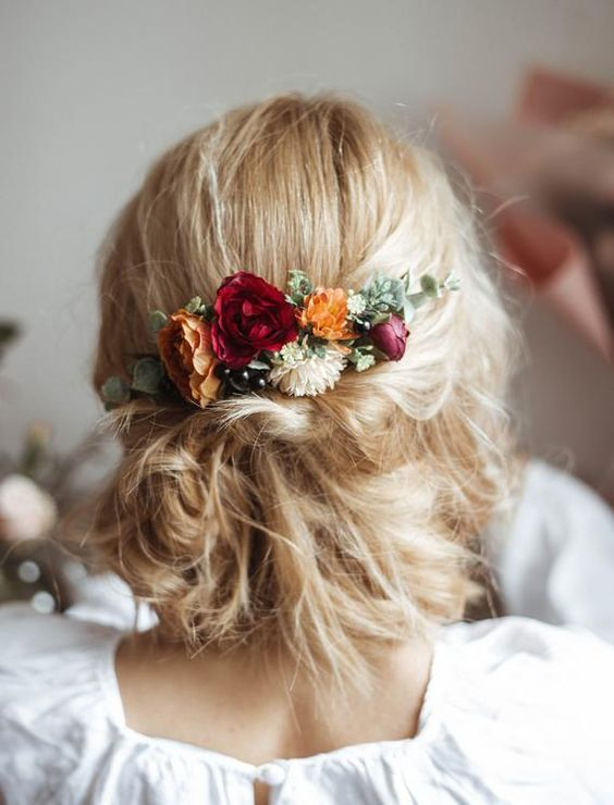 a messy low updo with textural hair and bright fall blooms and greenery is a gerat idea for both fall and summer weddings