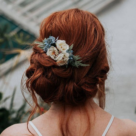 a messy low updo with twists and locks down with a bump on top and neutral and blue blooms and greenery