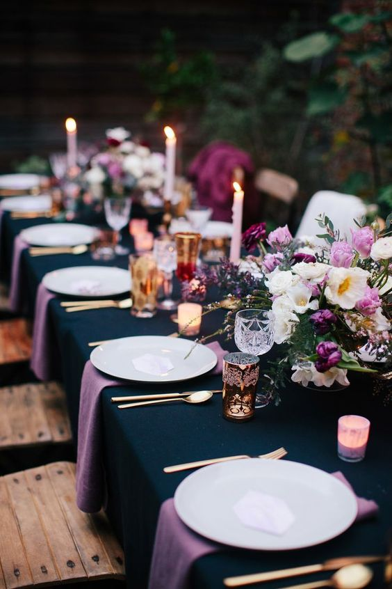 a midnight blue tablecloth loks very chic with purple napkins and purple and pink blooms