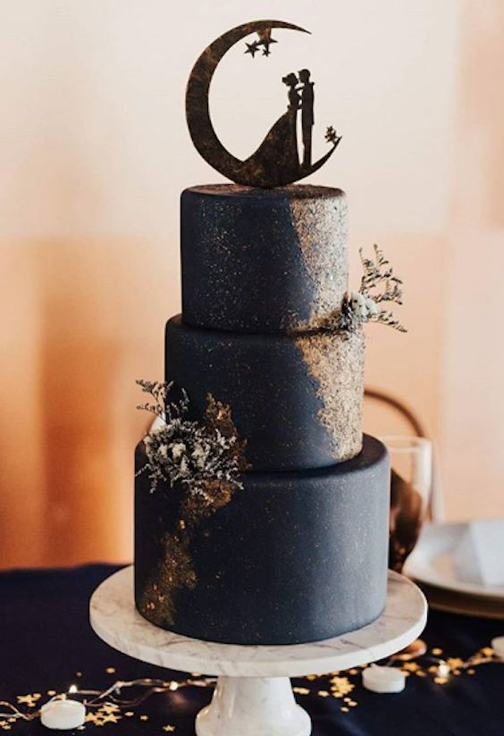 a midnight blue wedding cake with metallic decor and dried leaves and herbs and a romantic moon topper