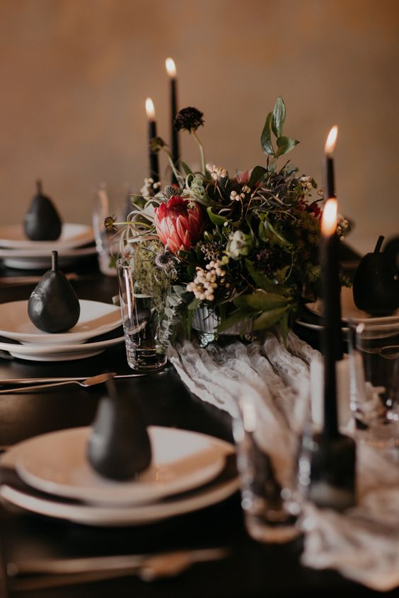 a modern Halloween wedding table setting with a black tablecloth, candles and pears, greenery and deep colored blooms