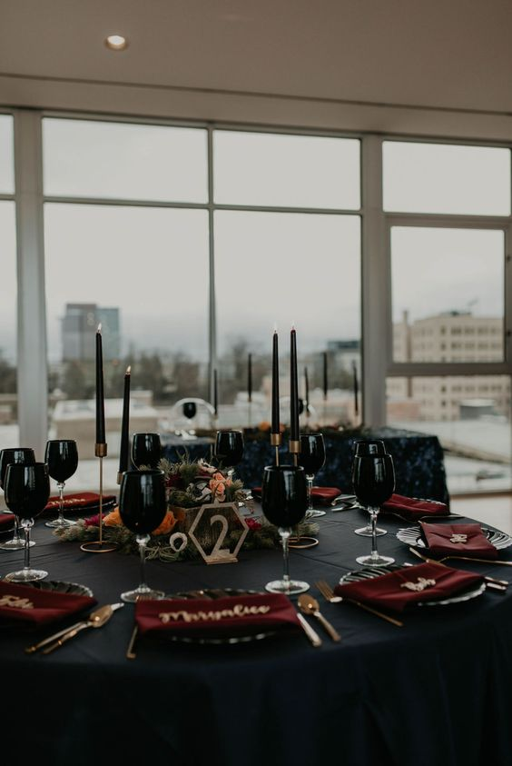 a modern Halloween wedding tablescape with a black tablecloth, candles, glasses, burgundy napkins and touches of gold
