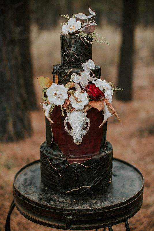 a moody Halloween wedding cake in black and burgundy, with white and bright blooms, dried leaves, patterns and a sugar skull