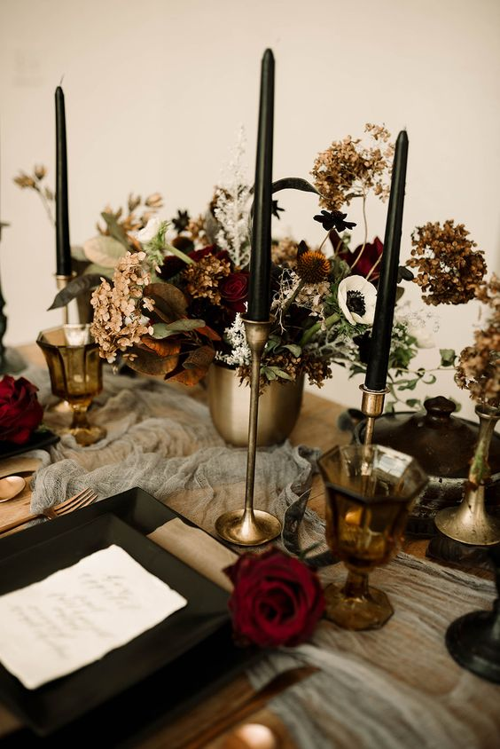 a moody Halloween wedding tablescape with a grey runner, black plates and candles, gold vases and candleholders