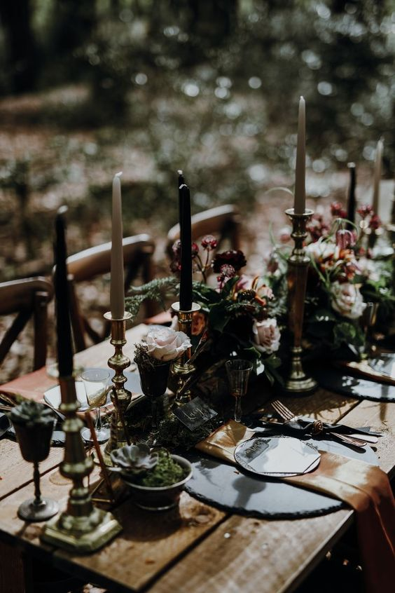 a moody and refined Halloween wedding table with gold napkins, black and white candles, greenery, succulents and blush roses