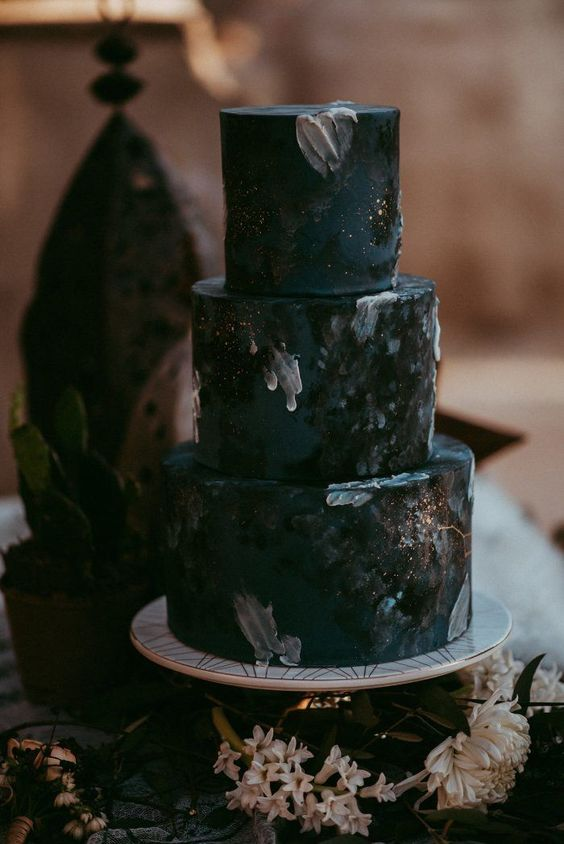 a moody black wedding cake with glitter and brushstrokes and much texture is chic for Halloween
