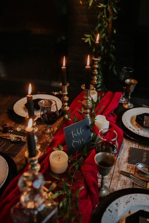 a moody luxurious wedding tablescape with a red table runner, black candles, gold touches and greenery