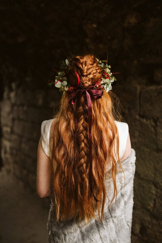 a pretty half updo with messy and textural braids on top and wavy locks down plus a greenery and fall floral crown with a burgundy bow
