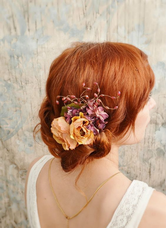 a pretty messy and loose wedding low updo with a bump and some locks down and with rust-colored and purple blooms