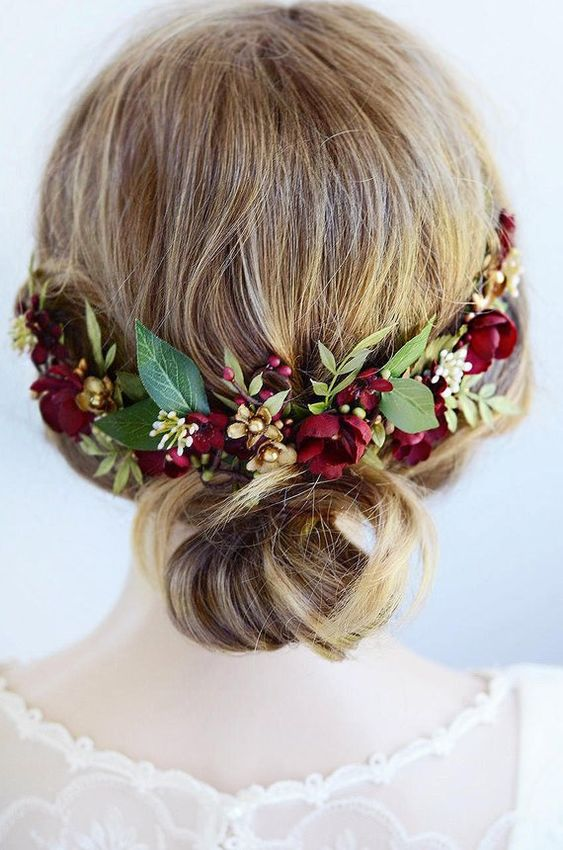 a pretty wedding low bun on medium length hair accented with burgundy blooms and greenery is a lovely and comfy idea