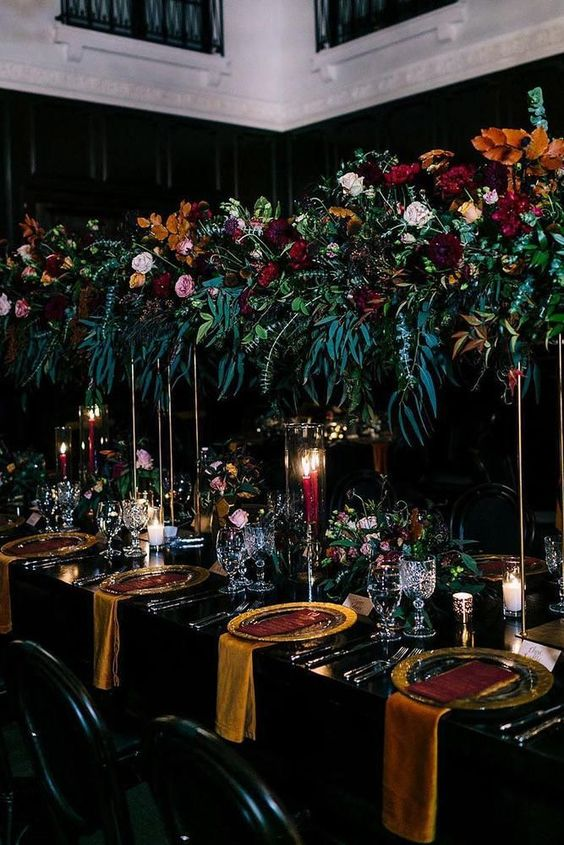 a refined Halloween wedding table setting with a black tablecloth, mustard napkins and chargers, lush floral and greenery arrangements