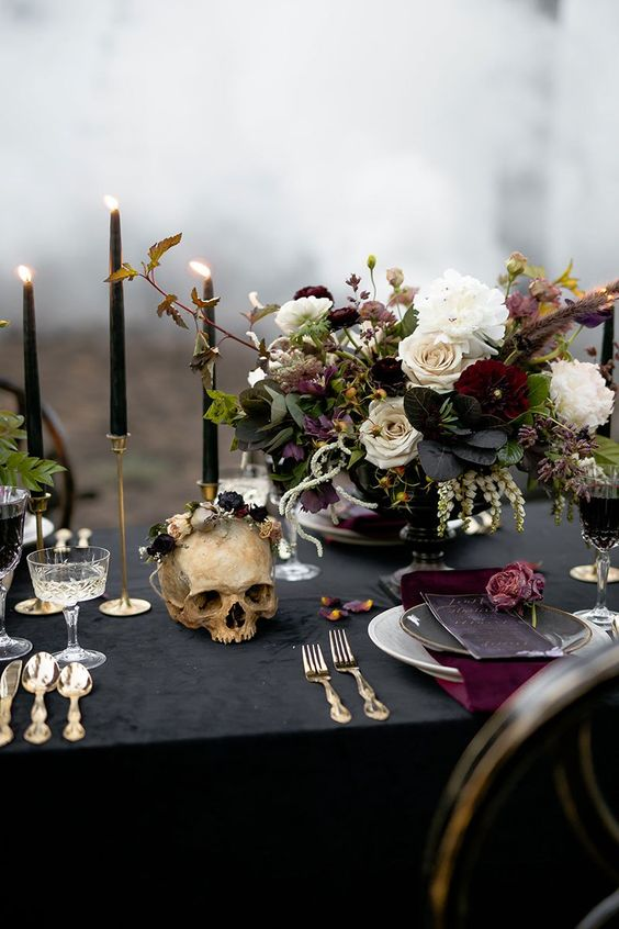a refined Halloween wedding table with a black tablecloth and candles, burgundy napkins, a chic floral centerpiece, gold cutlery and a skull