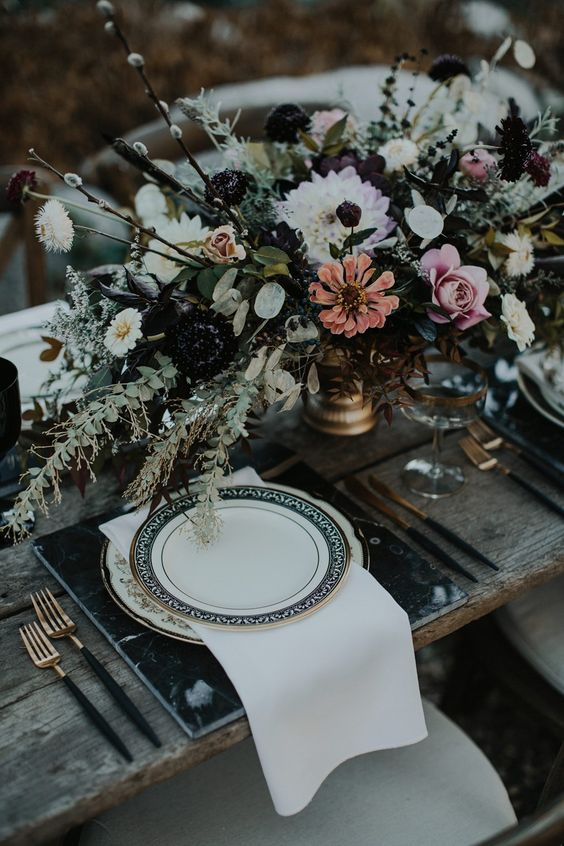 a refined Halloween wedding table with black marble chargers, black cutlery, a lush floral arrangement with greenery
