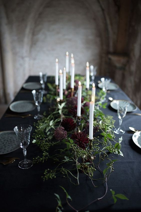 a refined Halloween wedding tablescape with a black tablecloth, printed plates, lush greenery and deep purple blooms and candles