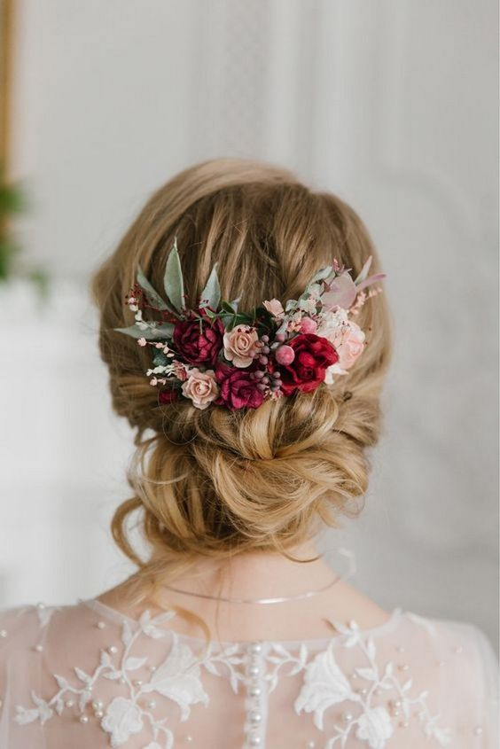 a refined low updo with twists and some waves down and bold blooms - fuchsia, blush and pink flowers, greenery
