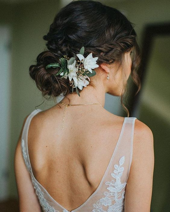 a refined wedding low bun with twists and a braid, with white blooms will match a fall and a summer wedding