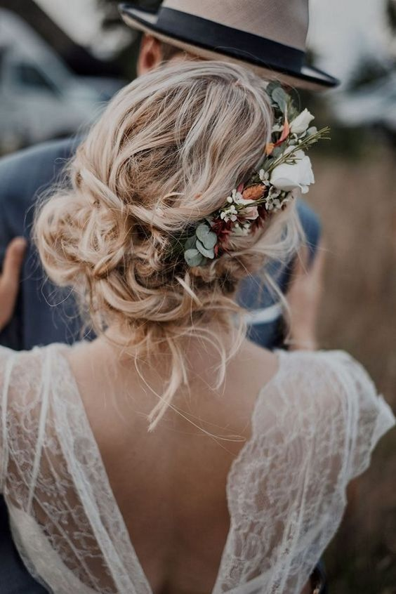 a relaxed and messy low bun with waves down and a neutral flower accent with greenery for a fall boho wedding