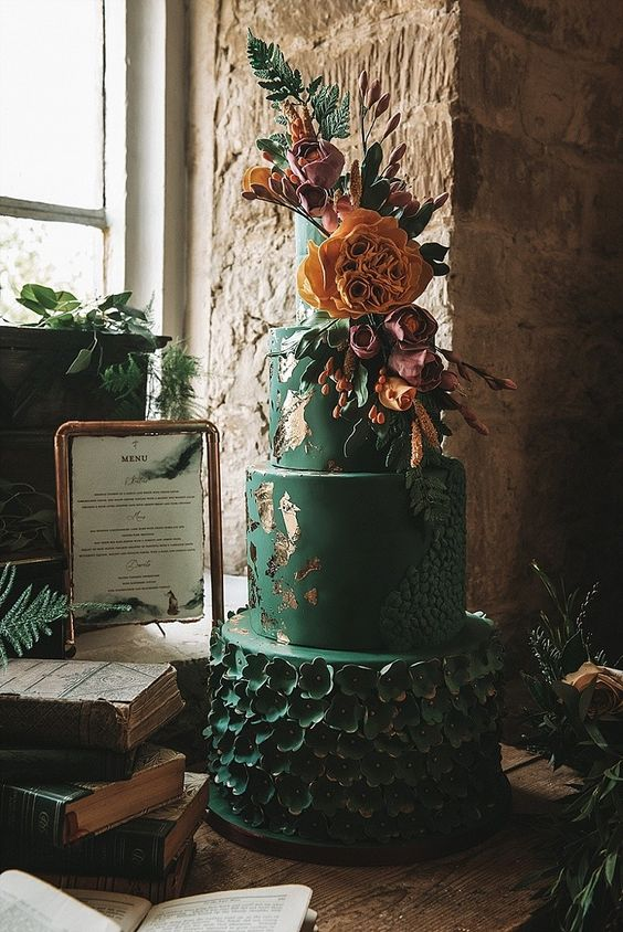 a romantic black wedding cake with gold leaf, sugar blooms, bright flowers and greenery for a Halloween wedding