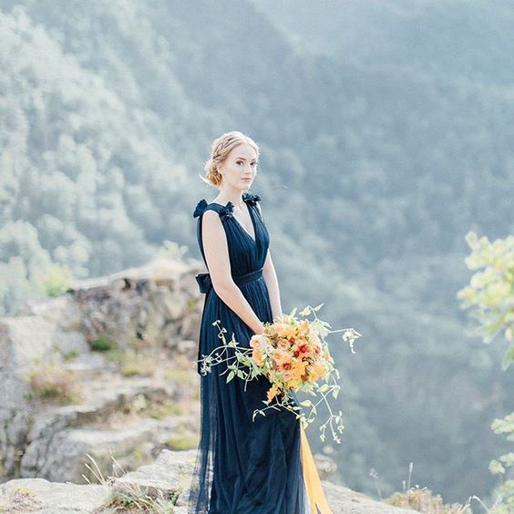 a romantic midnight blue wedding dress with thick straps and appliques, a bow on the back looks very bold