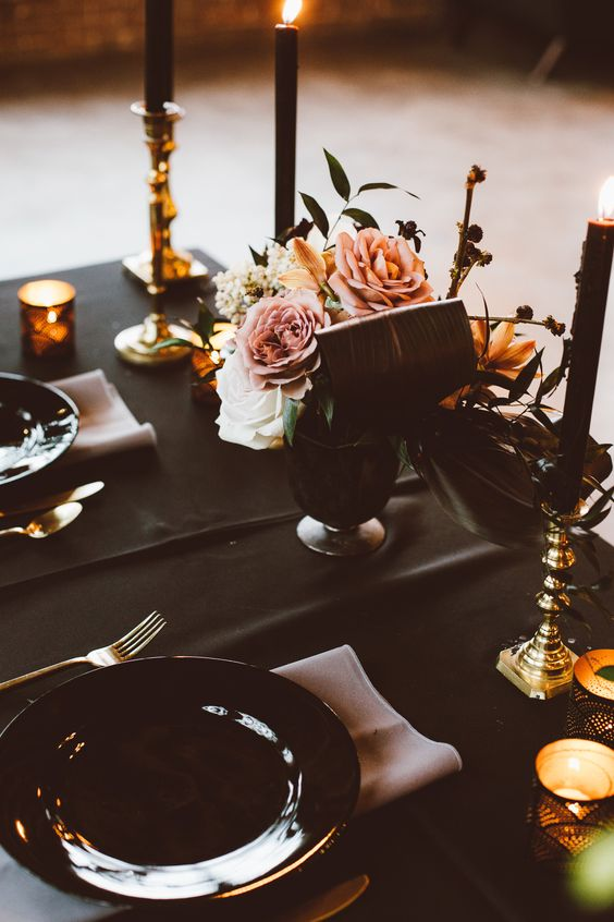 a soft gothic Halloween tablescape with a black tablecloth, plates and candles, blush blooms and napkins plus gold touches
