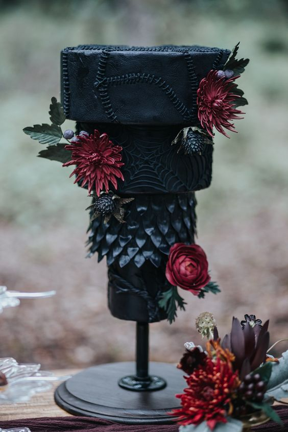 a statement Halloween wedding cake in black, with scars, spiderwebs, scallops and burgundy blooms and leaves