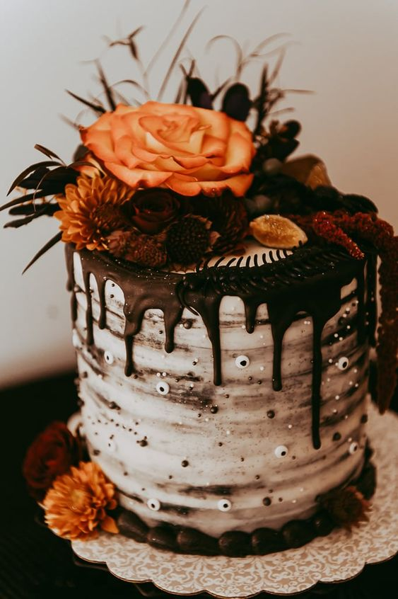 a stylish and chic Halloween wedding cake with chocolate drip, googly eyes, berries and fruit plus bright blooms
