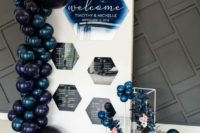 a stylish contemporary seating chart with hexagons, mignight blue and black baloons and some blue flowers