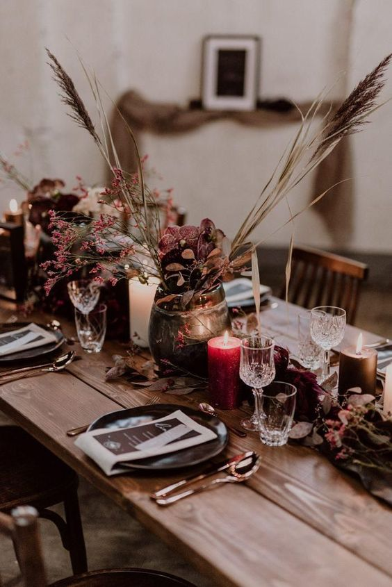 a sumptuously colored Halloween wedding tablescape with black plates, fuchsia and purple blooms and grasses and red candles