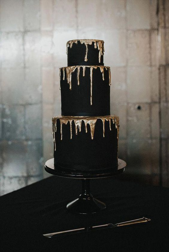 a super chic black wedding cake with gold drip is a very elegant and chic piece for a Halloween wedding
